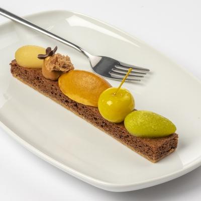 Herfstplankje met peer, appeltje, grote caramelmousse, puntje hazelnootpraliné, kleine canelle appel en puntje peer